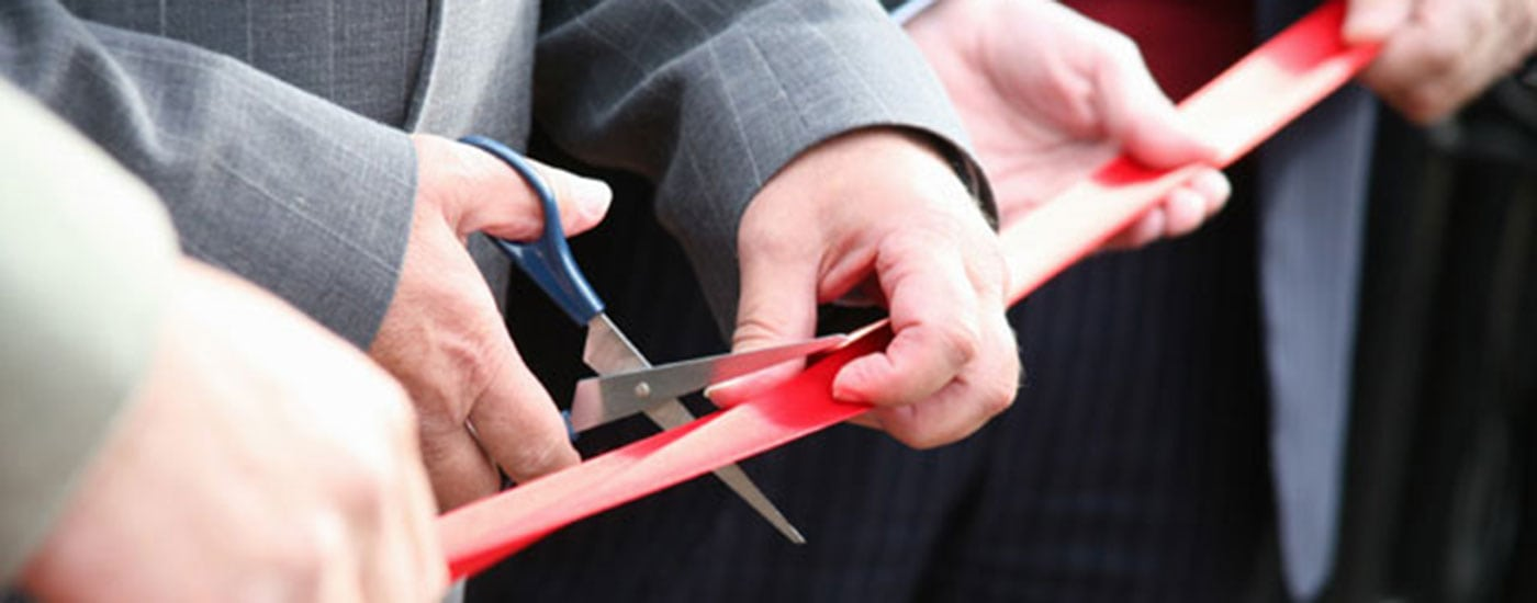 Businessmen in a ribbon cutting ceremony