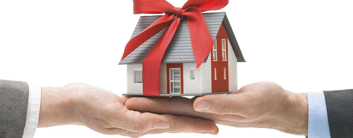 Handing off a house with a gift bow