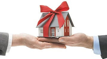 Hand holding a house that has a gift bow on it