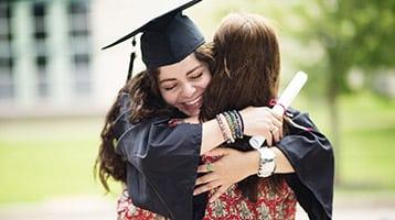 A graduate hugging her mother