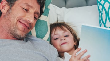 A father and daughter read in bed