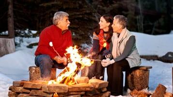 family circling a campfire