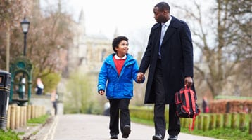 Image of father and son walking and holding hands