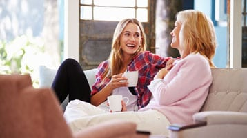 Image of mother and daughter sitting on the couch and talking