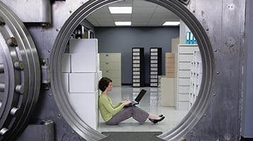 Woman sitting inside a vault with her laptop