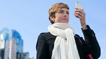 woman stands outside looking at smartphone