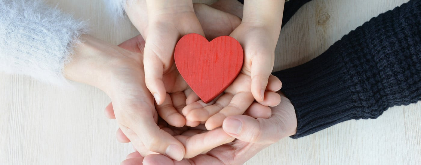 multiple hands holding a wooden heart