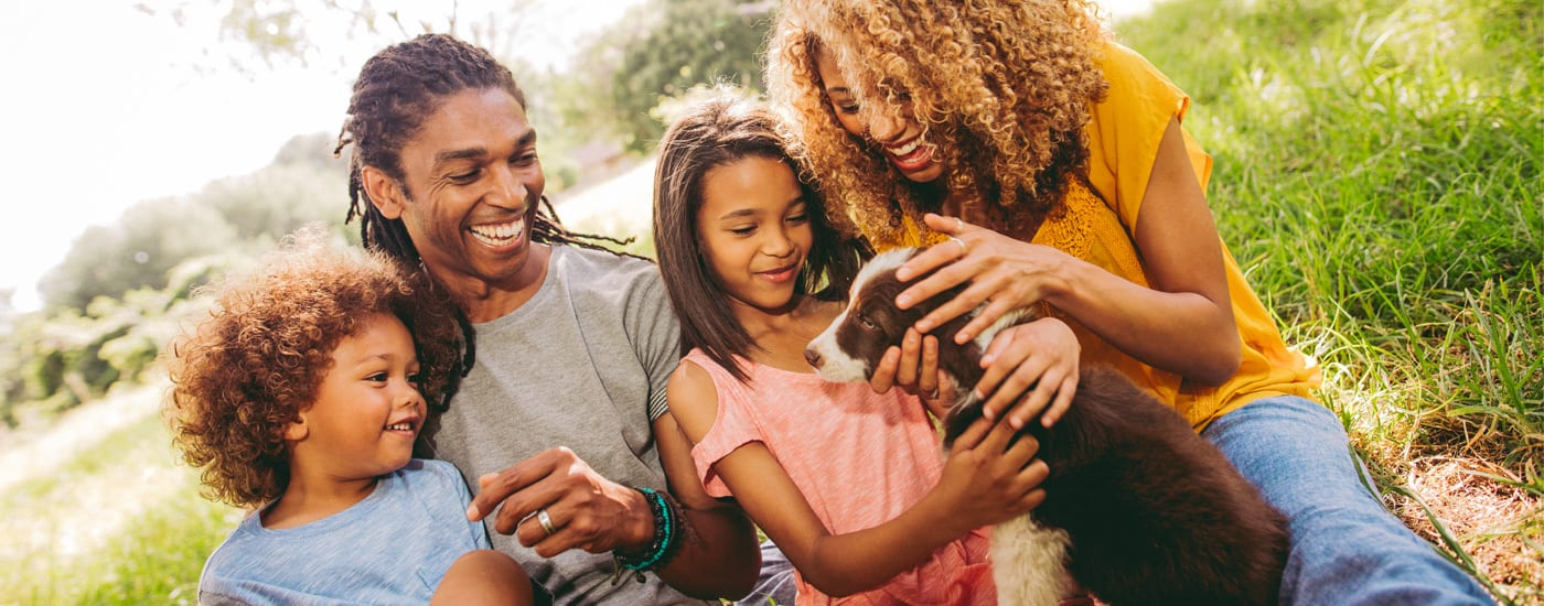 Image featuring a happy young family as they gather around a puppy.