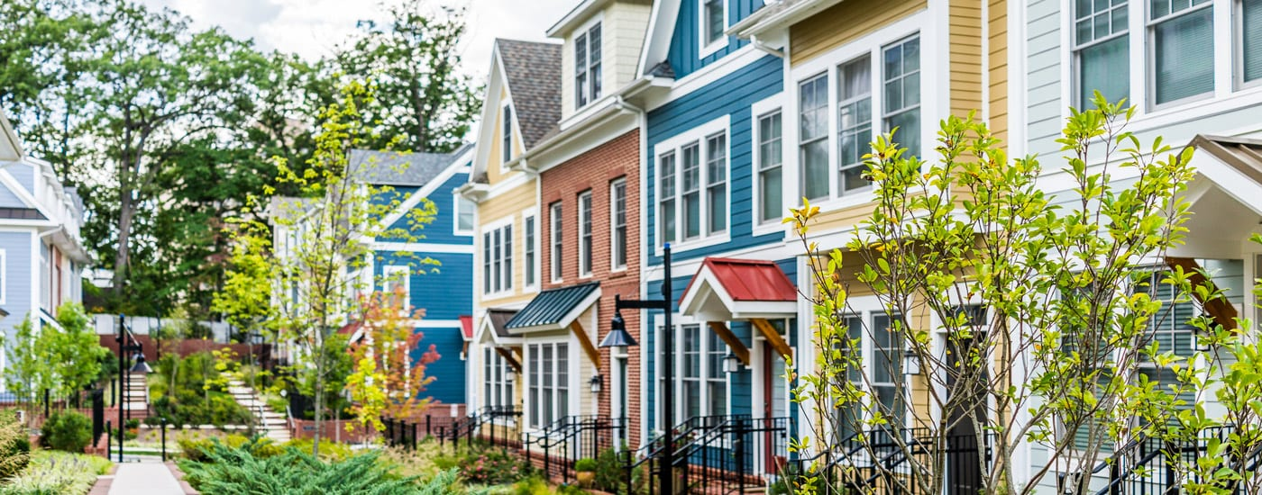 Image shows a row of brightly painted three-story homes to represent one type of income-producing property