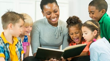 A happy woman reads to children.