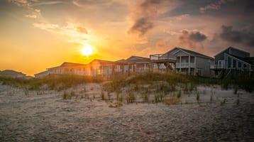 sun setting over a row of beach properties