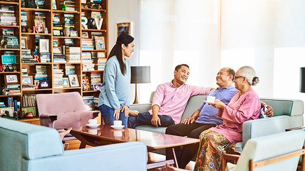 Parents and adult children gathered in the living room discuss ways to bridge generational gaps in decisions about family wealth management.