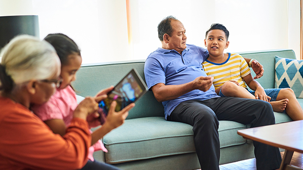 Children and their grandparents sit in the living room and discuss topics related to family wealth management.