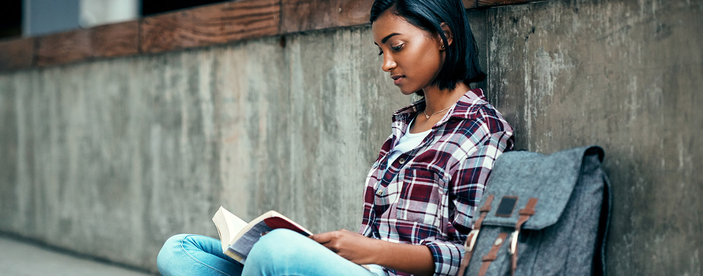 A young woman with a backpack reads a book.