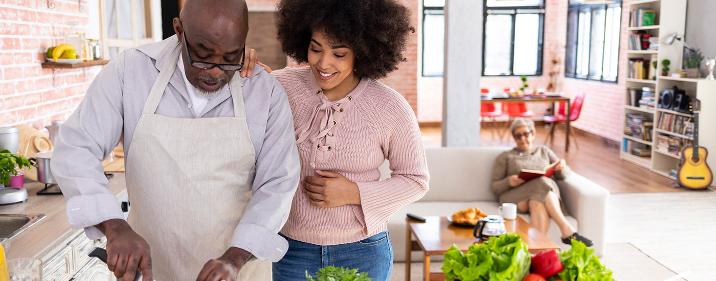 A woman helps her father make a salad.