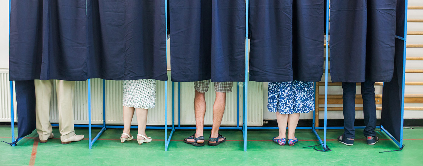 Voters behind curtains cast their ballots at a polling place.
