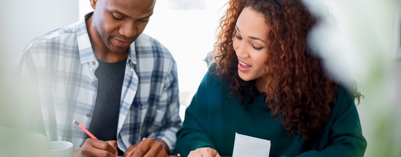 A man reviewing paperwork helps his daughter prepare a budget.