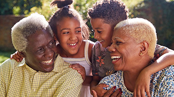 Smiling children and their grandparents gather close to each other.
