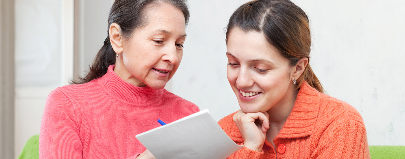 A woman and her adult daughter review some paperwork.
