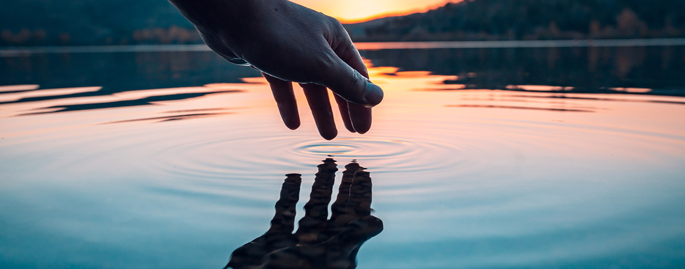 A hand hovers above water as the sun sets in the background.