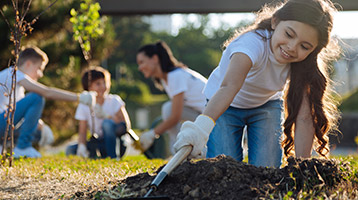 A girl uses a garden tool to till the soil.
