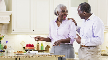 A man and a woman smile at each other in the kitchen.