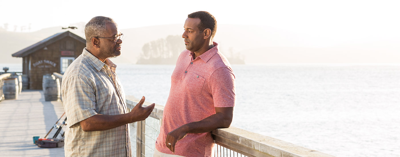 A man speaks to his son on a fishing pier.