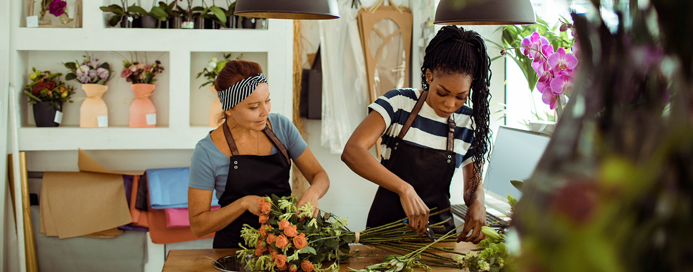 Two women work together creating flower arrangements.