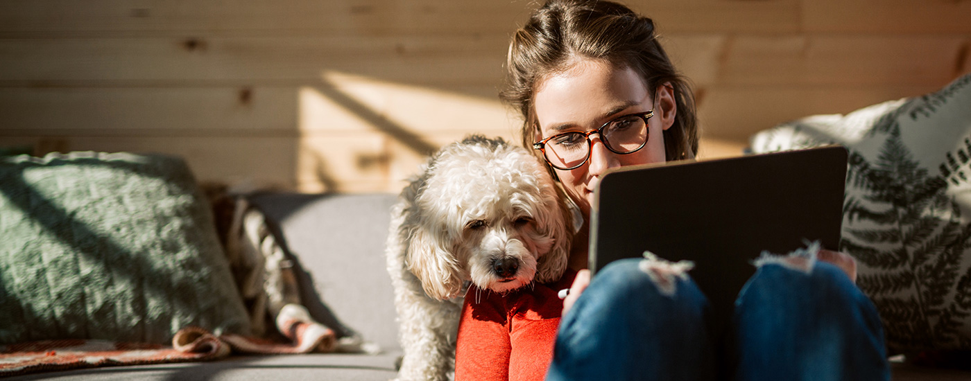 A college student with her dog nearby works on her tablet.