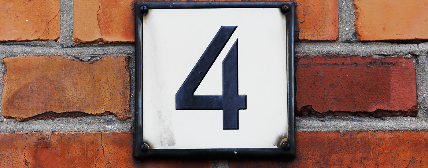 The number 4 on a brick wall near the entrance to a house.
