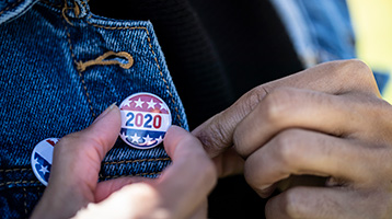 A woman holds a 2020 elections button.