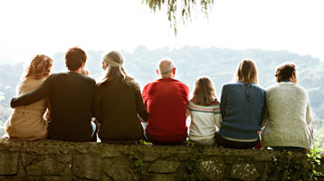 Family sits closely together outside.