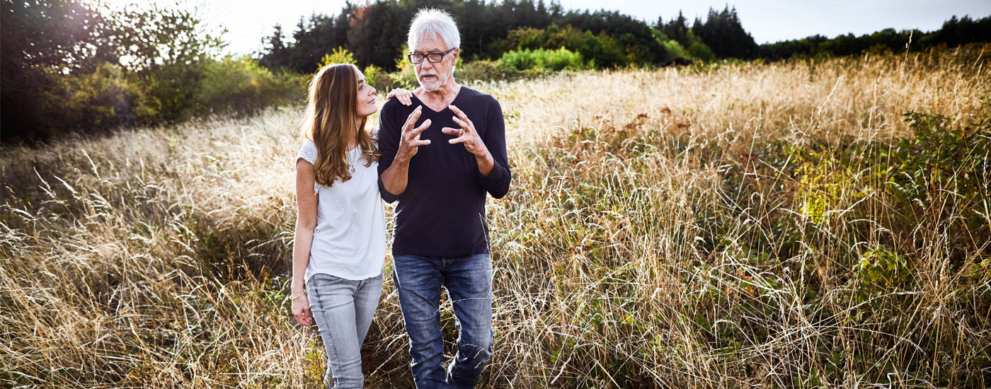 Adult daughter walking with father in a field